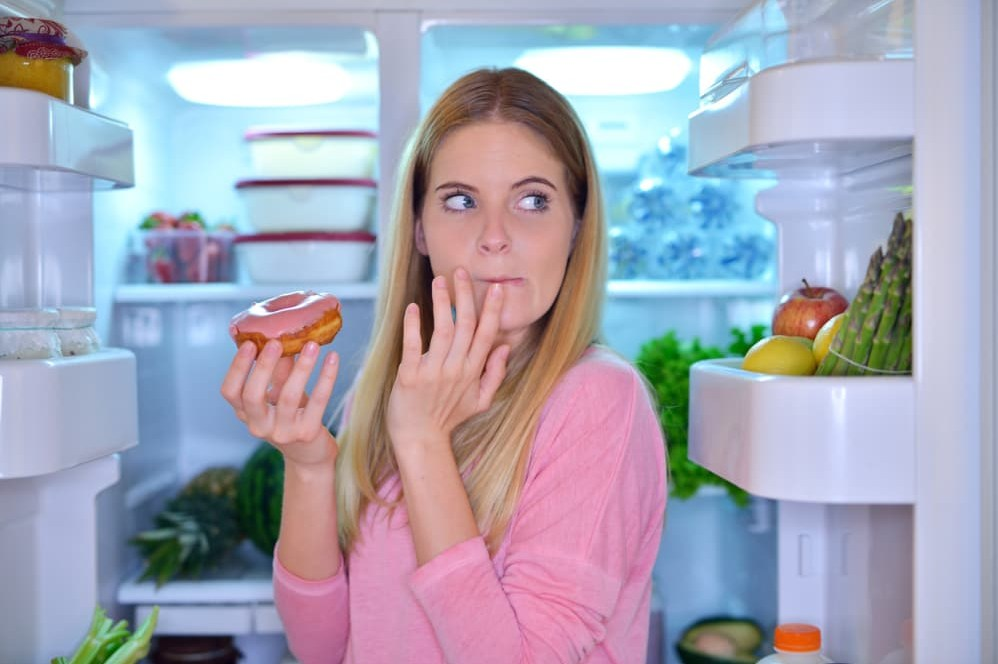 жена яден поничка пред хладилник