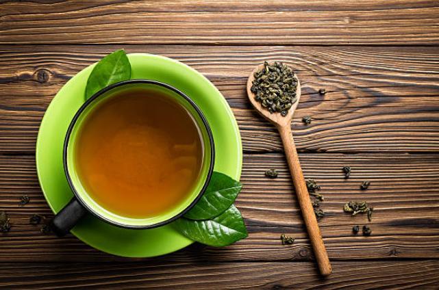 Чаша чай, лъжица и листа от зелен чай